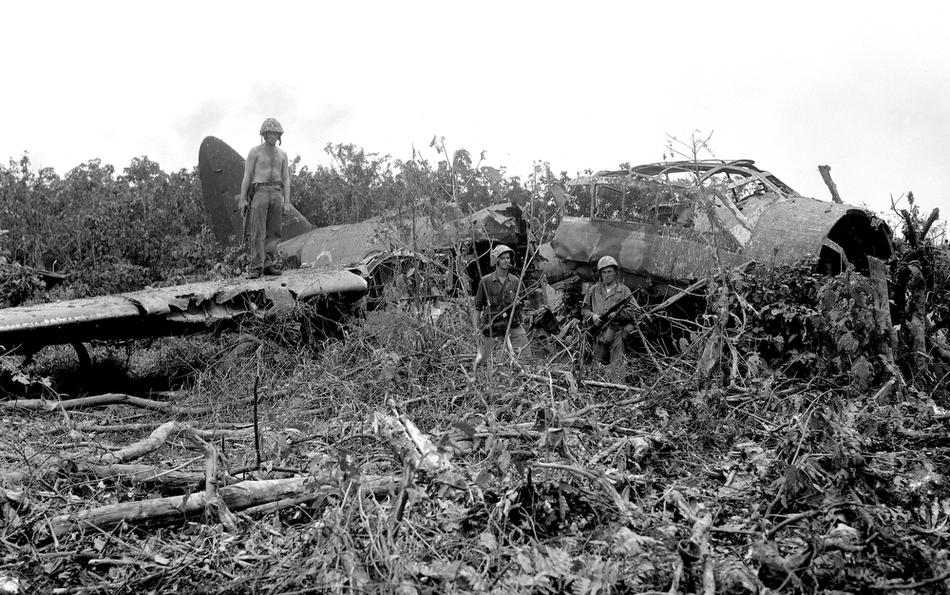 Soldiers stand by a crashed Japanese bomber on Peleliu, Republic of Palau, Sep. 22, 1944. (AP Photo/Joe Rosenthal)