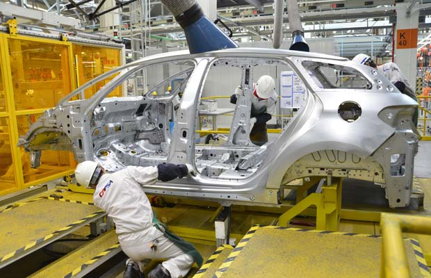Workers put together a car in a workshop inside the PSA Peugeot Citroen's fourth Chinese factory in Shenzhen, south China's Guangdong province on September 28, 2013. The company and its Chinese partner Changan kicked off local production of its biggest model to date, the DS5, at their Shenzhen plant. CHINA OUT AFP PHOTOSTR/AFP/Getty Images
